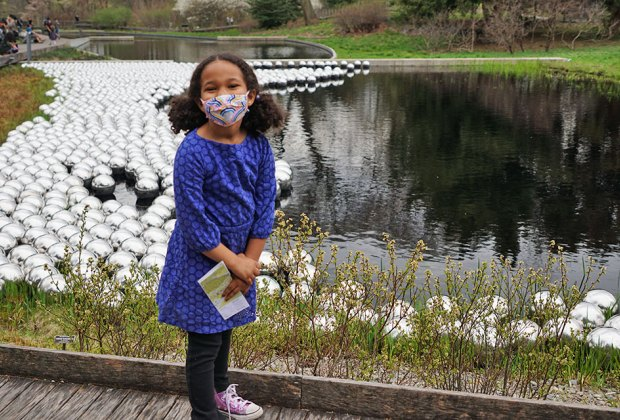 Girl standing near Kusama's Narcissus Garden in the Native Plant Garden at NYBG collection 1,400 stainless steel spheres