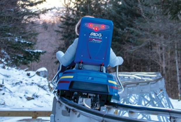 Cliffside Coaster riding down the hill on the coaster Things to Do in Lake Placid on a Winter Vacation Status message