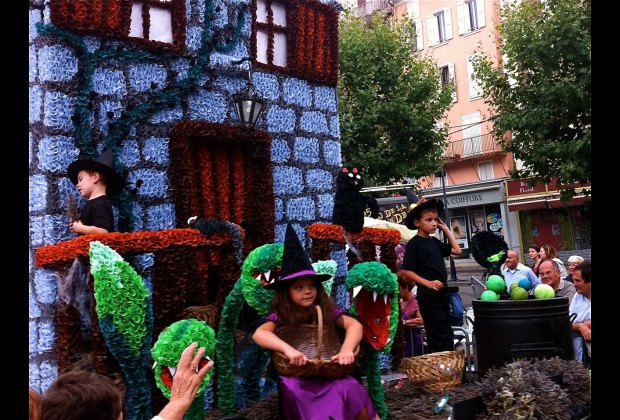 Local children throw bunches of lavender to the crowds from their floats