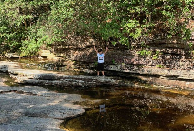 A boy poses on a rock outcropping near Awosting Falls in Lake Minnewaska State Park and Preserve