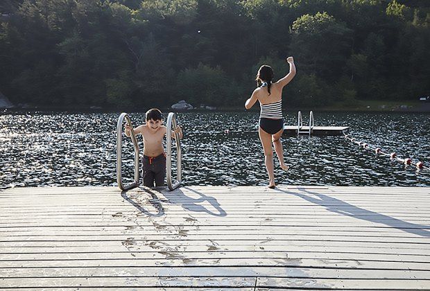 kids jumping off a dock into a lake