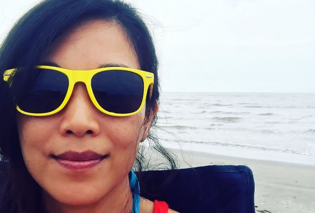 woman in bright yellow sunglasses on the beach