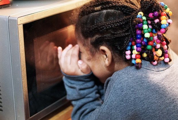 Girl peeks into microwave to check on a mug cake.