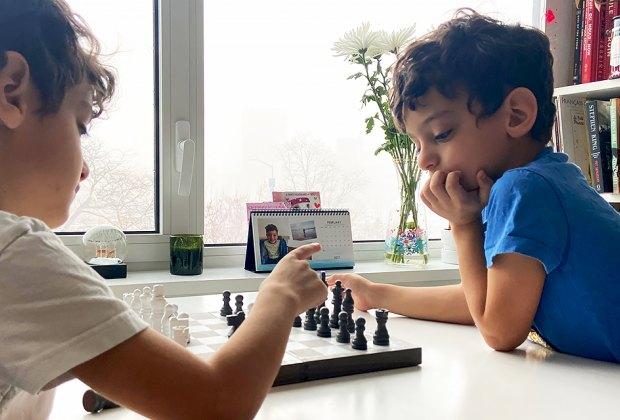 two boys playing chess LI spring break activities