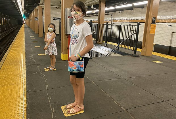 Two girls stand on empty New York City subway platform