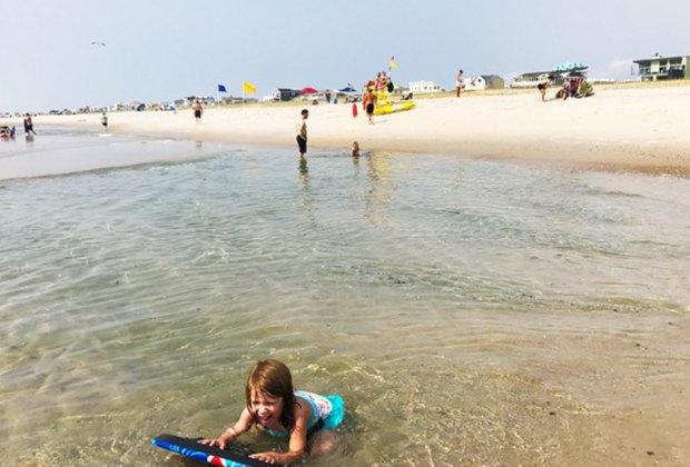 beach in nj girl in the water on floatie nj staycation