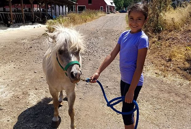 A girl leads a pony around Norz Hill Farm