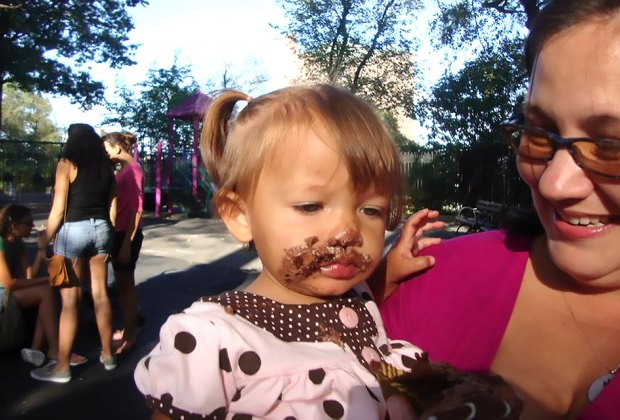 First birthday party baby with messy, cake-covered face