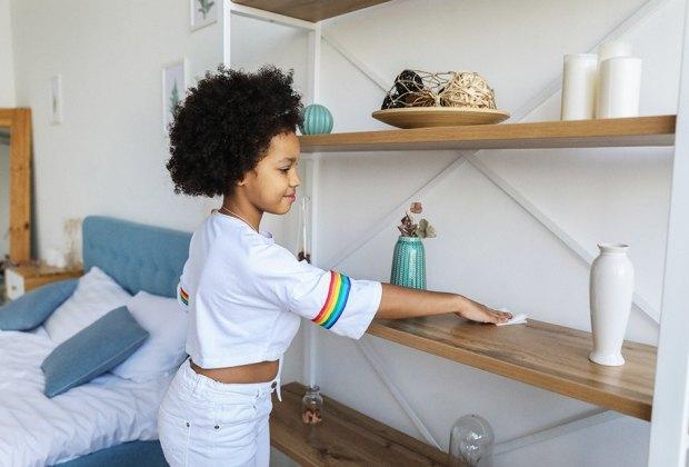 a girl dusting a shelf