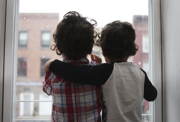 two boys looking out a window with their arms around each other