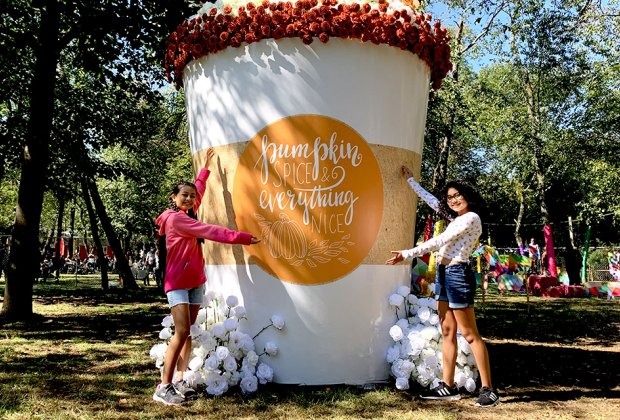 Two girls pose beside a larger-than-life pumpkin spice cup crafted out of flowers at The Fall Escape
