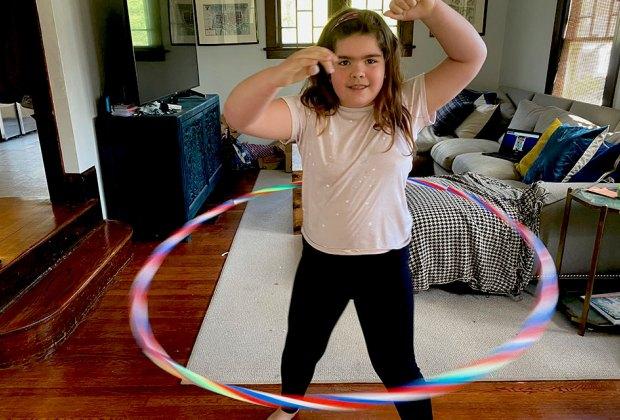 girl hula hoops inside indoors