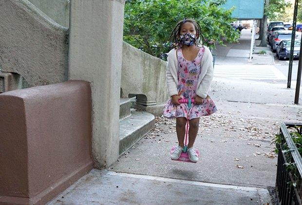 girl jumping on pogo stick on the sidewalk