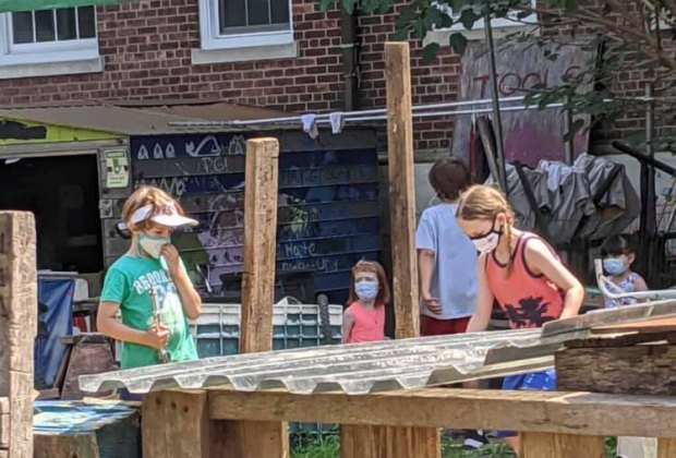 Masked children play in The Yard, Governors Island's adventure playground