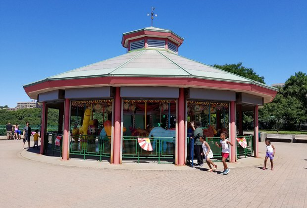 Wide shot of kids running around a carousel