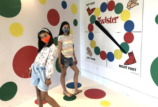 girls posing on giant twister board
