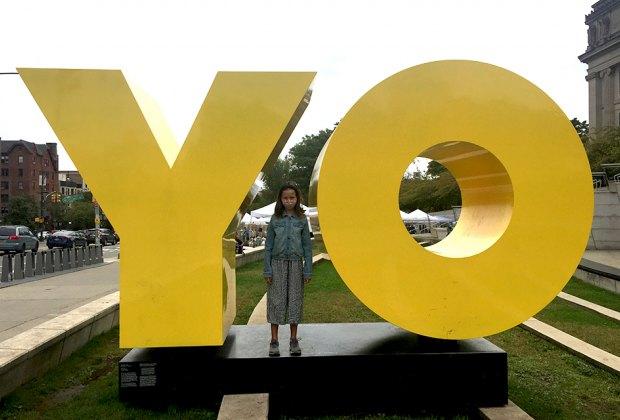 girl standing between YO sign