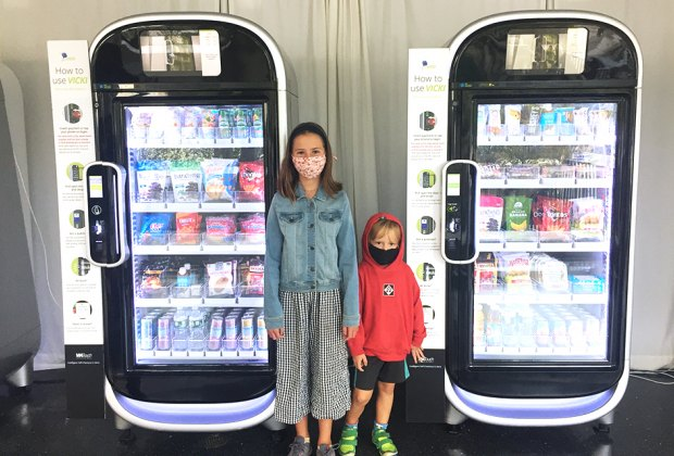 girl and boy kids standing at AI-inspired vending machines