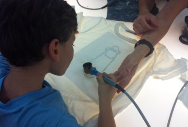 A hot wax gun is used to trace the sketch onto the T-shirt