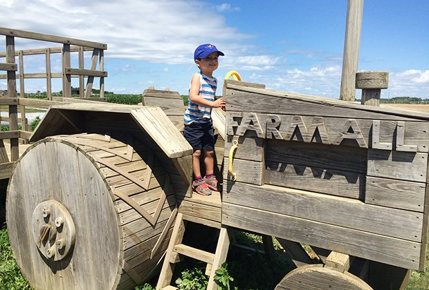 Boy rides a toy tractor at windy acres farm