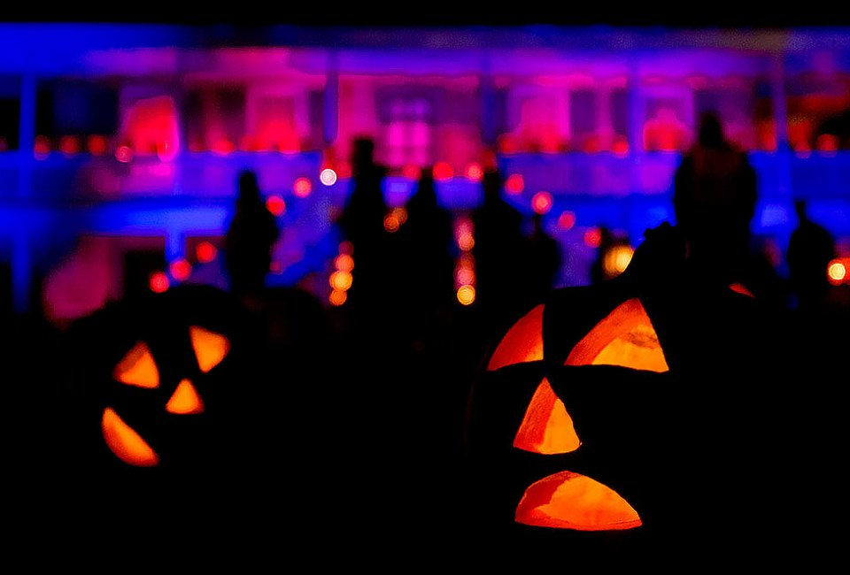 Jack-0'-lanterns line the lawn in front of the manor house.